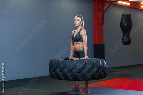 Fit female athlete working out with a huge tire, turning and carry in the gym. Crossfit woman exercising with big tire - 227202531