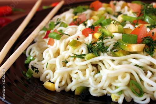 seasoned noodles on a plate with chopsticks - 227205745