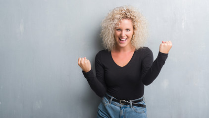 Young blonde woman with curly hair over grunge grey background screaming proud and celebrating victory and success very excited, cheering emotion