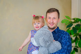 Portrait of funny little girl and her father at home. Family, childhood and leisure concept