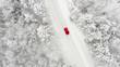 canvas print picture - rotes Auto auf einer schneebedeckten eisigen Straße im Winter von oben, Luftbildaufnahme