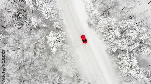 canvas print picture rotes Auto auf einer schneebedeckten eisigen Straße im Winter von oben, Luftbildaufnahme