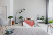 Leinwandbild Motiv Armchair and carpet in apartment interior with plants and lamp next to bed with red sheets. Real photo