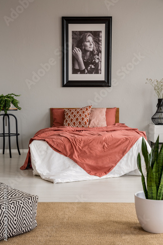 Leinwandbild Motiv Poster on grey wall above bed with red sheets in bedroom interior with pouf and plants. Real photo