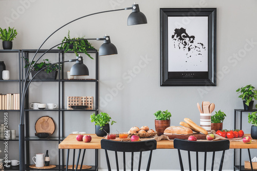 Black lamp above wooden table with eco food in grey dining room interior with plants and poster. Real photo