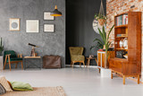 Flat interior with texture, black and brick walls in real photo with retro cupboards, fresh plants, posters, briefcase and telescope on end table - 227242132