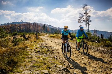 Mountain biking woman and man riding on bikes at sunset mountains forest landscape. Couple cycling MTB enduro flow trail track. Outdoor sport activity.