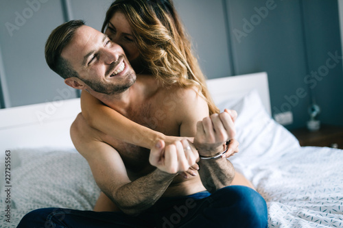 Back view of woman in black panties holding her bra while man is lying on bed - 227255563