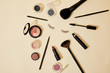 top view of different cosmetics lying on beige surface around false eyelashes