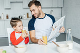 father with newspaper looking at son drinking juice during breakfast in kitchen - 227267913