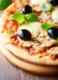 Pizza with mozzarella, mushrooms, black olives and fresh basil. Italian pizza. Homemade food. Symbolic image. Concept for a tasty and hearty meal. Rustic wooden background. Selective focus. Close up.  - 227270320