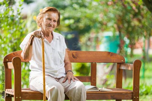 Leinwandbild Motiv Elderly woman sitting and relaxing on a bench in park