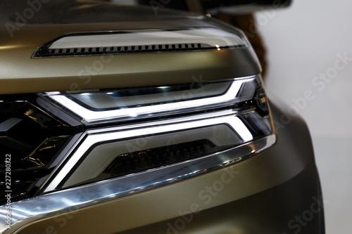 Headlight of modern prestigious car closeup. Car detail. Car headlights. Exterior detail - 227280322