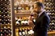Quadro Portrait of handsome elegant businessman drinking red wine in bar