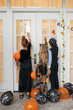 Quadro Rear view of kids wearing beautiful Halloween costumes standing on porch of the house and knocking on the door to ask for candies