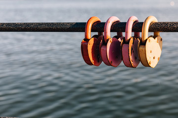 colorful locks hang on the pipe on the right side against the background of water © Poel Kashi
