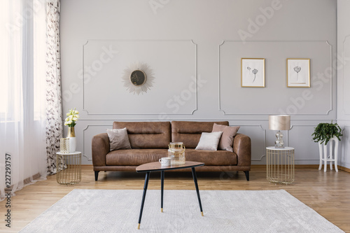Wooden table on carpet in front of leather sofa in grey living room interior with posters. Real photo - 227293757