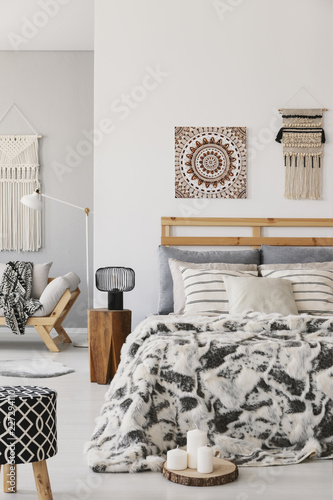 Leinwandbild Motiv Patterned stool and lamp next to bed with cushions in scandi bedroom interior with poster. Real photo