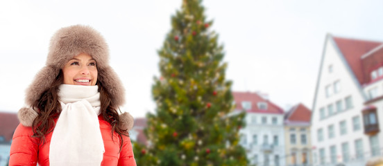 people, season and leisure concept - happy woman in winter fur hat over christmas tree at tallinn old town hall square background