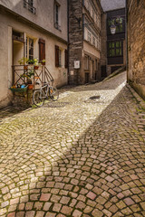 A back street in Saint Malo, Brittany, France, with a beam of sunlight lighting the cobbles. © Colin & Linda McKie