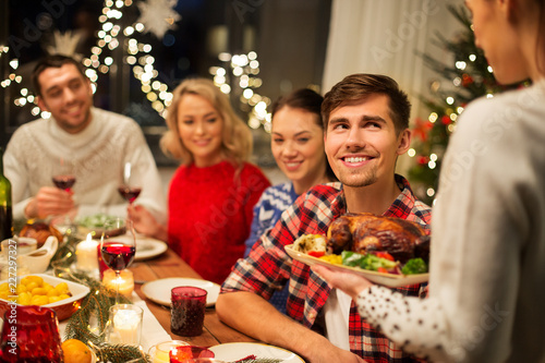 holidays and celebration concept - happy friends having christmas dinner at home - 227297327
