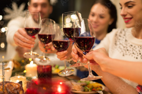 holidays and celebration concept - close up of happy friends having christmas dinner at home, drinking red wine and clinking glasses - 227297397