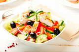 Chicken salad with cherry tomatoes, black olives, cucumber, red onion, red pepper, lettuce and fresh rosemary. Home made food Concept for a tasty and healthy meal Bright wooden background. Copy space  - 227298926