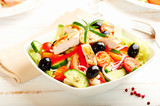 Chicken salad with cherry tomatoes, black olives, cucumber, red onion, red pepper, lettuce and fresh rosemary. Home made food Concept for a tasty and healthy meal Bright wooden background. Copy space  - 227299106