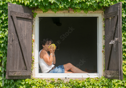 Foto Murales Woman sitting at window and drinking a tea