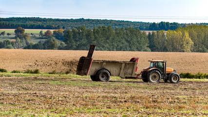 tracteur agricole qui fait un épandage de fumier sur le champ
