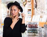 Adult woman customer in hat trying earrings
