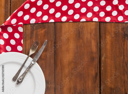 Empty white plate, fork and knife on the wooden table.