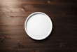 Blank white plate on wooden background. Flat lay.