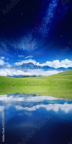 Vertical collage with green hill, high mountain, white clouds and deep blue space reflected in serene water