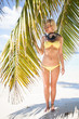 Blonde woman on sandy beach with snorkel equipment, Maldives