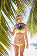 Blonde woman on sandy beach with snorkel equipment, Maldives