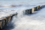 wooden groynes in the spray of the sea, smooth water by long exposure, nature background with copy space - 227337774