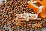 Cup of coffee with steam, coffee beans, chocolate pieces, cinnamon sticks, white and brown sugar, and scoop on burlap background.