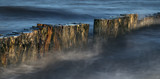 wooden groynes in the blue sea, smooth water by long exposure, nature background with copy space in panoramic banner format - 227340158