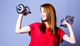 Girl in red t-shirt with metal dumbbells on gray background - 227345964