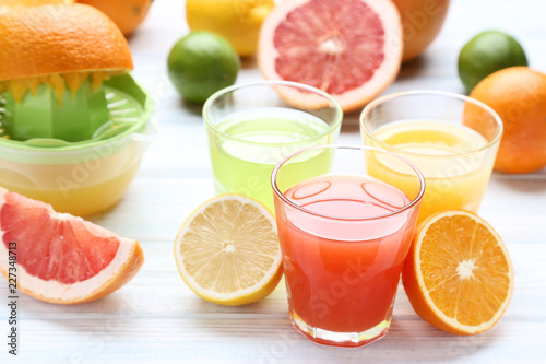 Foto Murales Citrus juice in glasses with fruits on white wooden table