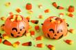 Quadro Halloween candy corns in pumpkin buckets on green background