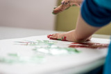Toddler child making colourfull palm prints