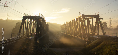 Leinwanddruck Bild A railway bridge in the morning fog or smoke through which the rays of the sun shine