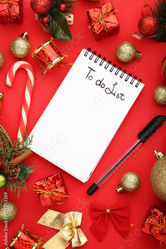 to do list in notepad with christmas decorations on red background