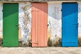 Few old wooden colorful doors on shabby light wall background - 227354112