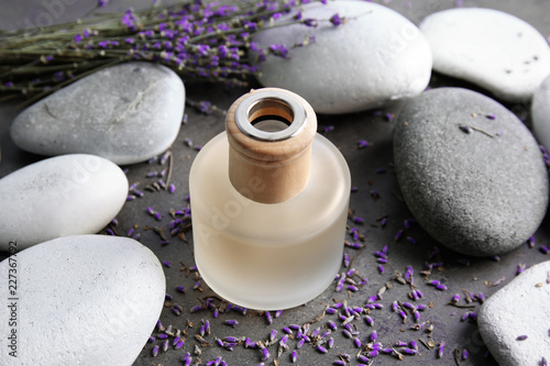Natural herbal oil and lavender flowers on grey background © New Africa