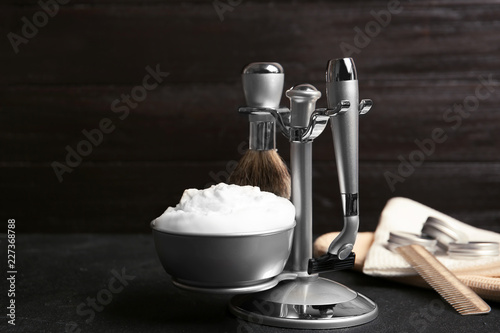 Shaving accessories on table against dark background with space for text © New Africa