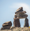 Inukshuk on rock against a cloudy blue sky