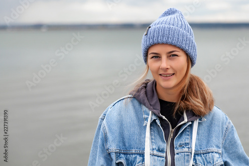 Leinwanddruck Bild Fashion lifestyle portrait of young trendy woman dressed in warm stylish clothes  laughing and smiling in the   sea, autumn street fashion.  portrait of joyful woman